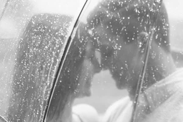mulher e homem debaixo de sombrinha na chuva