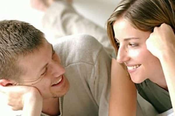 homem olhando para mulher deitados na cama e sorrindo